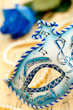 Venice mask. Blue and white carnival mask on a music paper with blue rose and white pearl Stock Image
