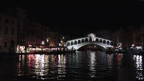Venice, night illumination, famous Rialto Bridge, Italy. Beautiful view of the Grand Canal at night. Reflections on the