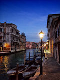 Venice at night with lamplight reflected in the water boats and. Darkening evening sky with a single star historic old buildings along and empty walkway Royalty Free Stock Image