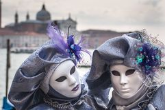Venice Purple Masks. Venice Carnival, two persons white mask and purple costume with bay and church in background royalty free stock photo