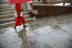 Venice in rain. It is raining cats and dogs and at red dressed lady is hurrying by along a canal in Venice, Italy. -  Motion blur Royalty Free Stock Photography