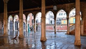 Venice rainy day with colorful corners, old buildings, historical open fish market with wet floor and classic columns , Italy royalty free stock images