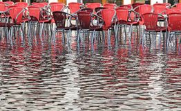 Venice, red chairs with water at high tide Royalty Free Stock Photo