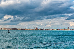 Venice Shoreline Under Gray Clouds. View of Venice Shoreline in Distance with Blue Water in Foreground and Dark Gray Clouds Overhead in Sky, Venice, Italy Stock Photos