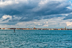 Venice Shoreline Under Gray Clouds. View of Venice Shoreline in Distance with Blue Water in Foreground and Dark Gray Clouds Overhead in Sky, Venice, Italy Royalty Free Stock Photos