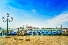 Venice, street lamp and gondolas or gondole and church on background. Italy stock images