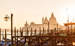 Venice sunset back light with gondolas and Cathedral background. Venice sunset back light with gondolas and Santa Maria della Salute church in background royalty free stock photography