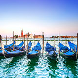 Venice sunset, gondolas or gondole and church on background. Italy Stock Images