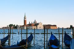 Venice Trademark Lagoon with gondolas close-up and venetian church on the bottom, at sunset Royalty Free Stock Photos