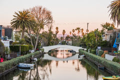 Venice, USA - December 25, 2015: Italian-like canals in Los Angeles during evening sunset with canoes and bridge Stock Photos