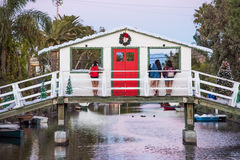 Venice, USA - December 25, 2015: Three women staring out of christmas decoration windows on canal bridge with wreath snow red door Royalty Free Stock Images