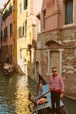 VENICE, VENETO, ITALY - Gondoliers and tourists, gondola riding, typical canal in Venice. September 21, 2017 Stock Photos