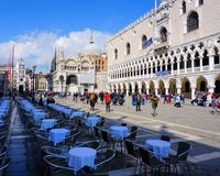 Venice, Veneto / Italy - March 2018: Tables sit mostly empty while tourists mill around St Mark`s Square near Doge`s Palace. royalty free stock photos