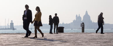 Venice - Walking on the waterfront and silhouette of Santa Maria della Salute church. Royalty Free Stock Image