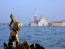 Venician statue on gondola. From a gondola, venician a statue in the foreground, giving way to the Venetian-channel Stock Photography
