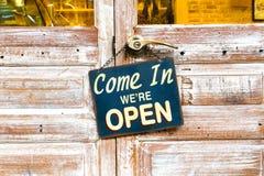 Venido adentro estamos abiertos en la puerta de madera centro de la foto HDR imagen de archivo libre de regalías