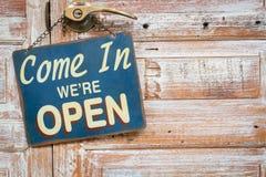 Venido adentro estamos abiertos en la puerta de madera, copyspace a la derecha fotografía de archivo