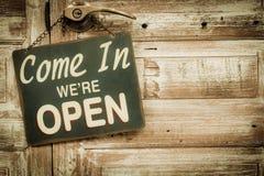 Venido adentro estamos abiertos en la puerta de madera, copyspace a la derecha V fotografía de archivo libre de regalías