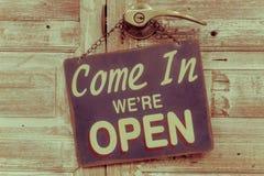Venido adentro estamos abiertos en la puerta de madera, estilo retro del vintage imagen de archivo libre de regalías