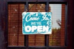 Venido adentro estamos abiertos Poste indicador gastado en estilo del vintage en una puerta vieja de la tienda foto de archivo