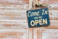 Venido adentro nosotros ` con referencia a abierto en la puerta de madera foto de archivo