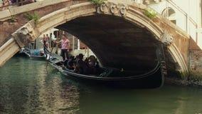 VENISE, ITALIE - 8 AOÛT 2017 Gondole vénitienne avec des touristes passant sous le petit pont Images stock