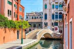 Venise, Italie : canal scénique avec un pont, des bâtiments colorés et des fleurs photographie stock
