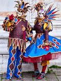 Venice, Italy - March 1, 2019 A couple is dressed with an Arlequin costume