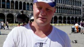 Venise, Italie - 7 juillet 2018 : le portrait du touriste heureux d'homme, tenant des pigeons, alimentant, jouent avec eux, ayant banque de vidéos
