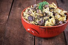 Venison or Beef Mushroom Stroganoff with Dill. Venison or Beef Mushroom Stroganoff with in a red ceramic serving bowl garnished with fresh dill over a rustic royalty free stock images