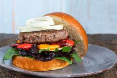 Venison burger in brioche bun. With peppery leaf salad, onion and roast peppers royalty free stock photography