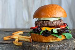 Venison burger in brioche bun. With peppery leaf salad, onion and roast peppers stock images