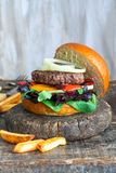 Venison burger in brioche bun. With peppery leaf salad, onion and roast peppers stock image