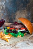 Venison burger in brioche bun. With peppery leaf salad, onion, roast peppers and lingonberry sauce stock photography