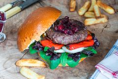 Venison burger in brioche bun. With peppery leaf salad, onion, roast peppers and lingonberry sauce royalty free stock photo