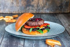 Venison burger in brioche bun. With peppery leaf salad, onion, roast peppers and lingonberry sauce stock photo