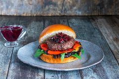 Venison burger in brioche bun. With peppery leaf salad, onion, roast peppers and lingonberry sauce stock photos