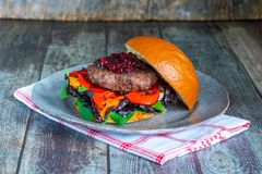 Venison burger in brioche bun. With peppery leaf salad, onion, roast peppers and lingonberry sauce royalty free stock photography