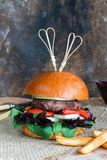 Venison burger in brioche bun. With peppery leaf salad, onion, roast peppers and lingonberry sauce stock image