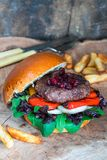 Venison burger in brioche bun. With peppery leaf salad, onion, roast peppers and lingonberry sauce stock images