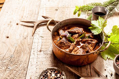 Venison Goulash in Copper Pot on Wooden Surface Royalty Free Stock Photos