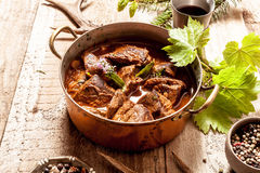 Venison Goulash in Copper Pot on Wooden Surface Stock Photos