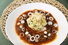 Venison goulash, onion circle and dumpling. Royalty Free Stock Photos