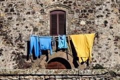 Venster en kleren het hangen Het oude huis van de muurvoorgevel Stock Afbeelding