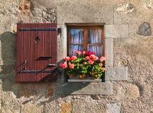 Venster met blinden en bloemen in de oude bouw in Zwitserland Stock Afbeelding