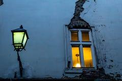 Venster met een barst en straatlantaarn in de avond in één van de kleine straten van Bratislava stock afbeeldingen