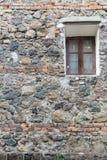Venster met een bruin kader op de muur van stoffige en roestige stenen, de oude achtergrond met een oud thema stock afbeeldingen