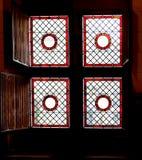 Venster met gebrandschilderd glas en houten blind stock afbeelding