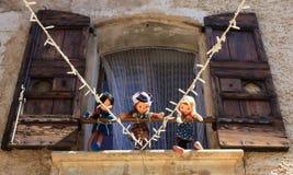 Venster met houten deuren, drie marionetten en lichten Royalty-vrije Stock Foto's