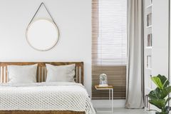 Venster met houten zonneblinden en lichtgrijs gordijn in witte bedroo stock fotografie
